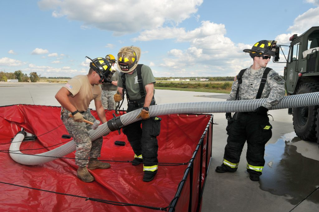 Firefighters training Army servicemen how to use a suction hose